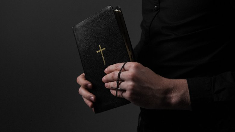 Bible in priest's hands