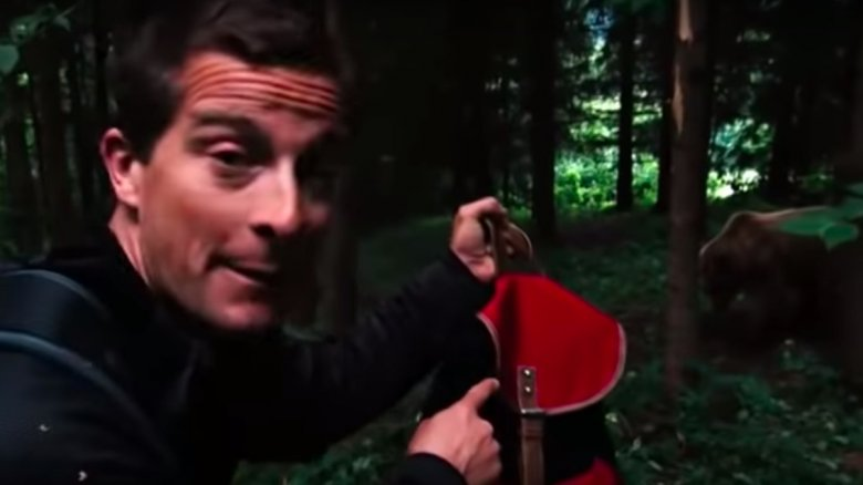Bear Grylls with a backpack and grizzly bear