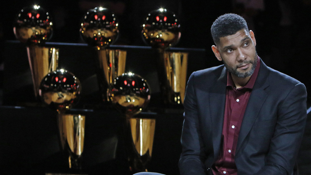 Tim Duncan in front of trophies