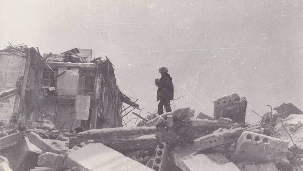 Man standing atop rubble in aftermath of the Spitak Earthquake